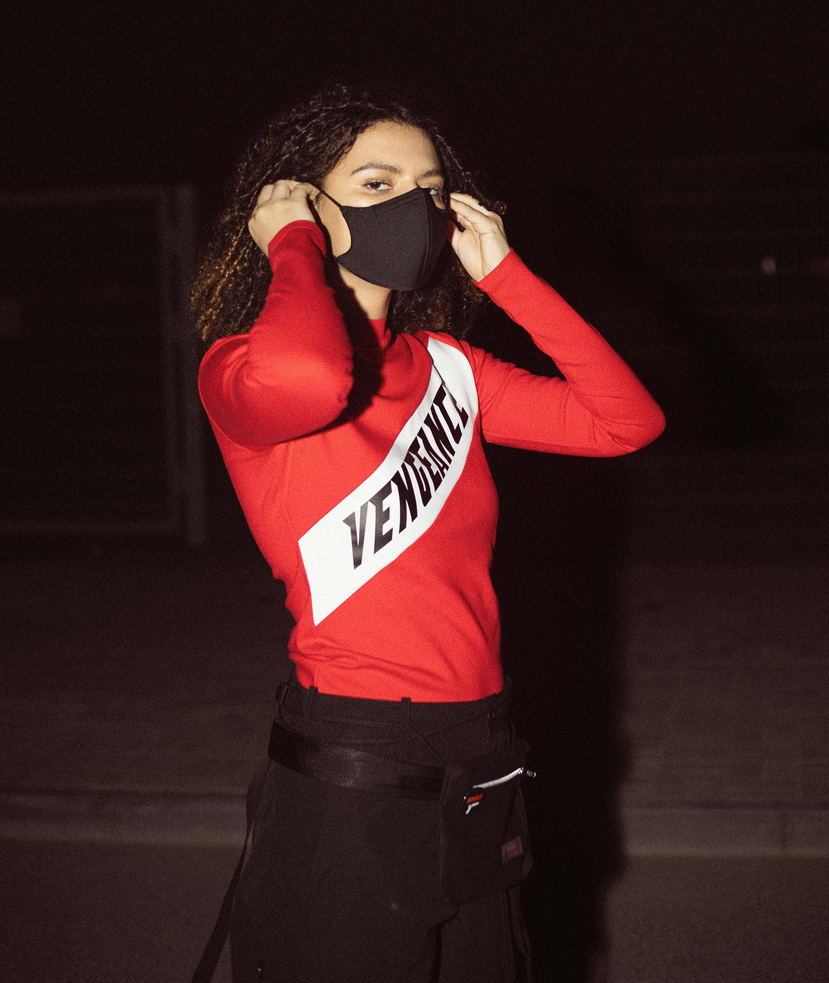 Model wearing red and black streetwear with the word vengeance written on the top